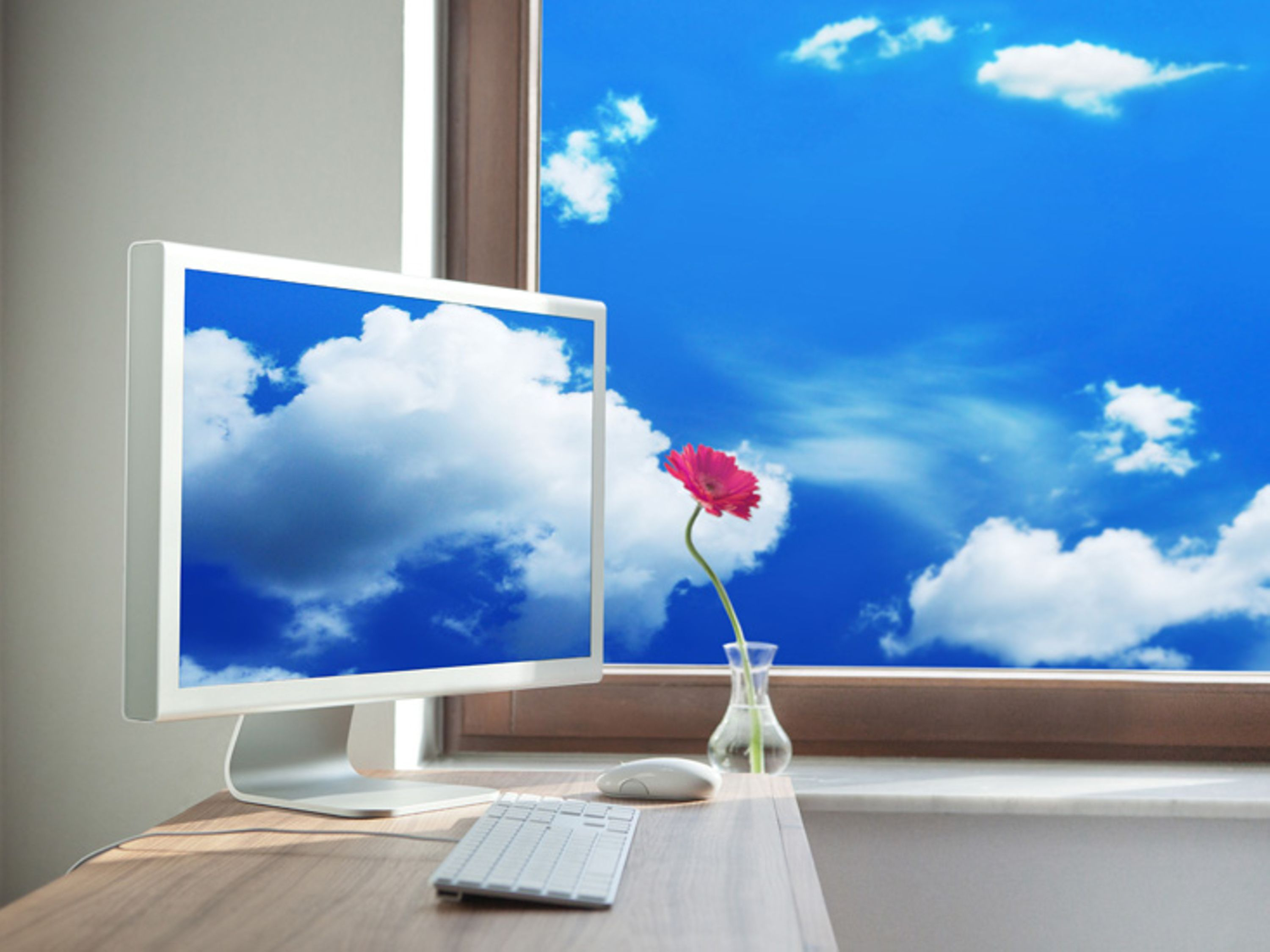 Clouds appear through a window and on a desktop