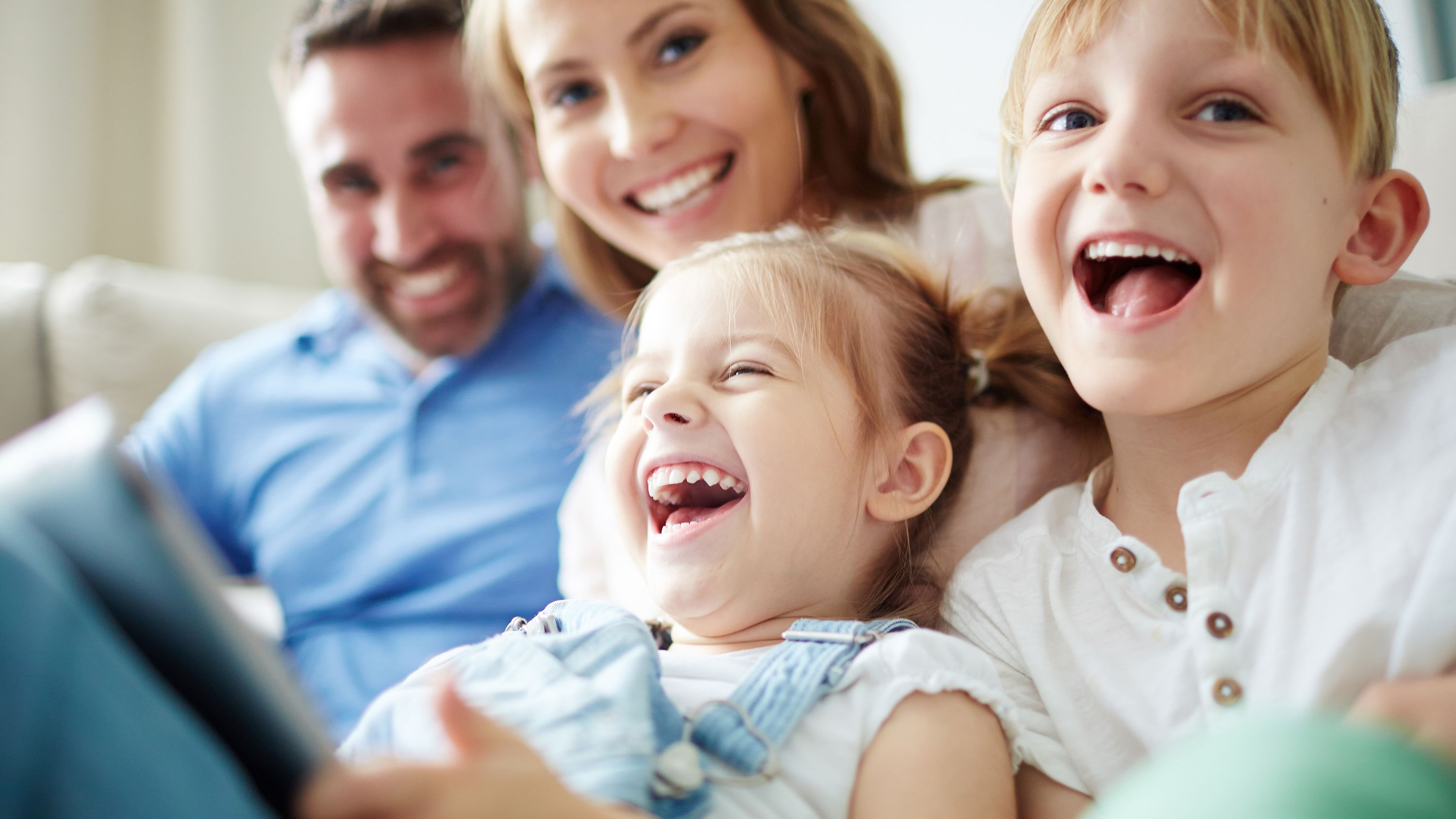 Cheerful family with laughing children on the couch