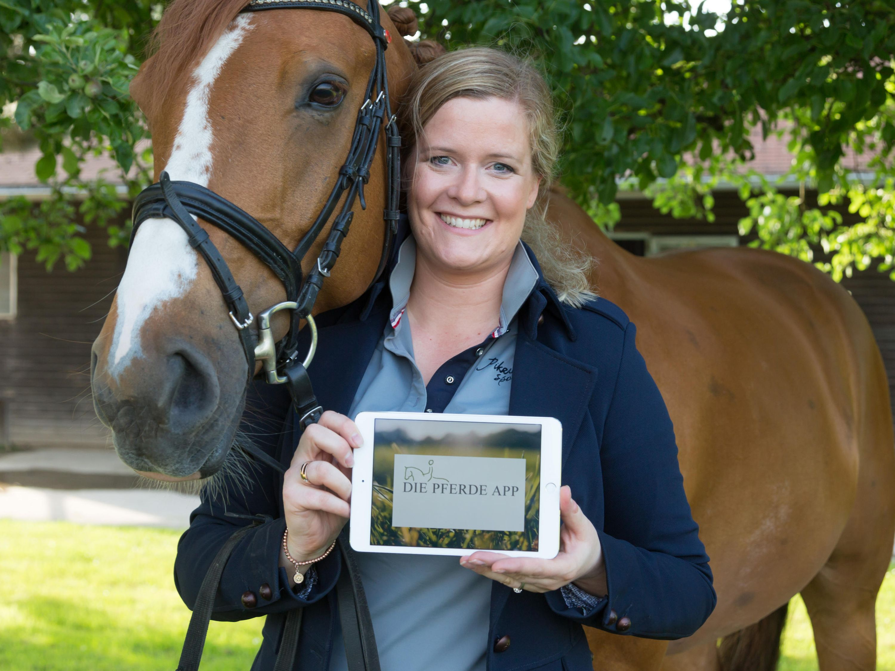 Christina Terbille and her horse Flo. The tablet is displaying her prototype app on screen.