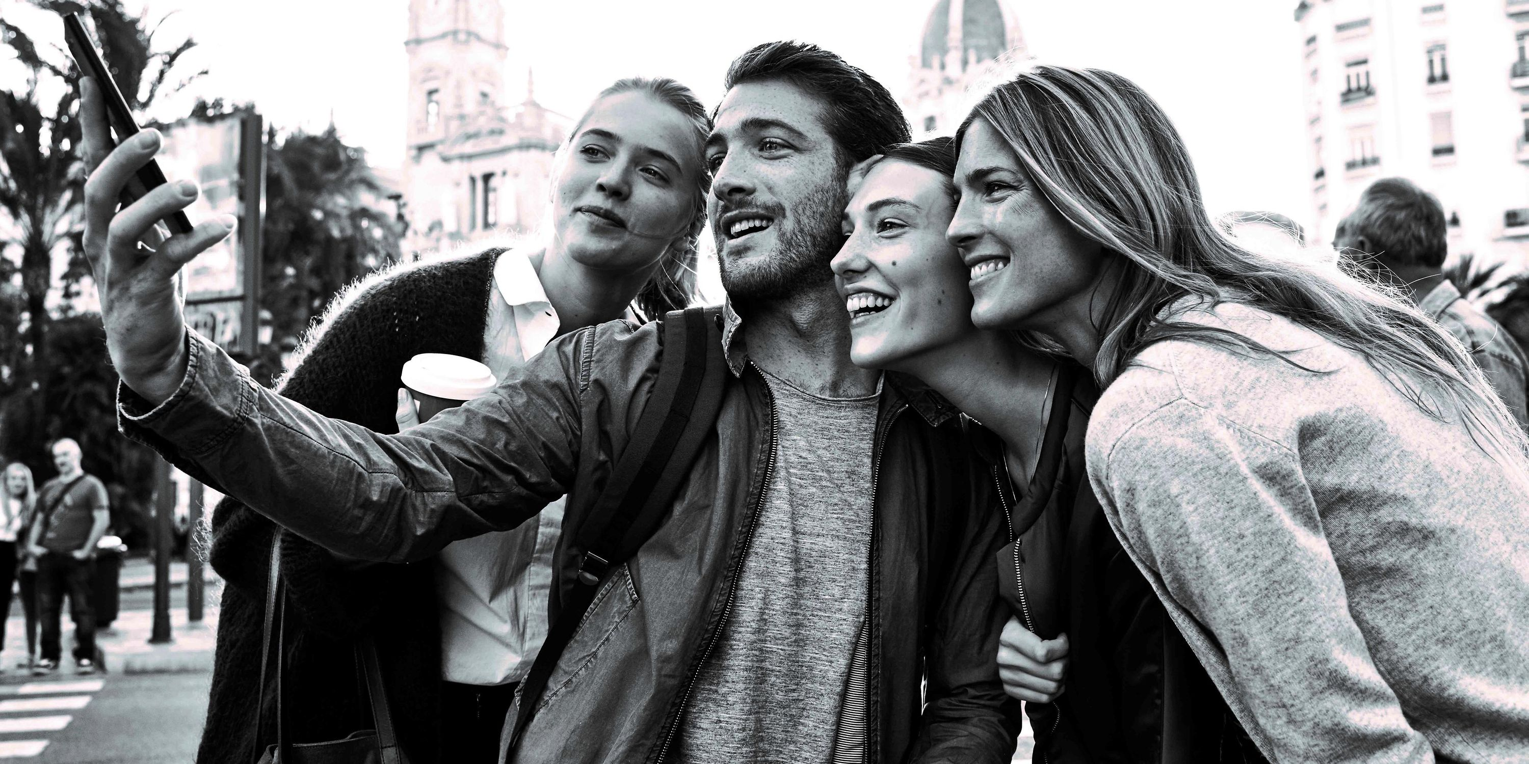 Four young people taking a selfie.