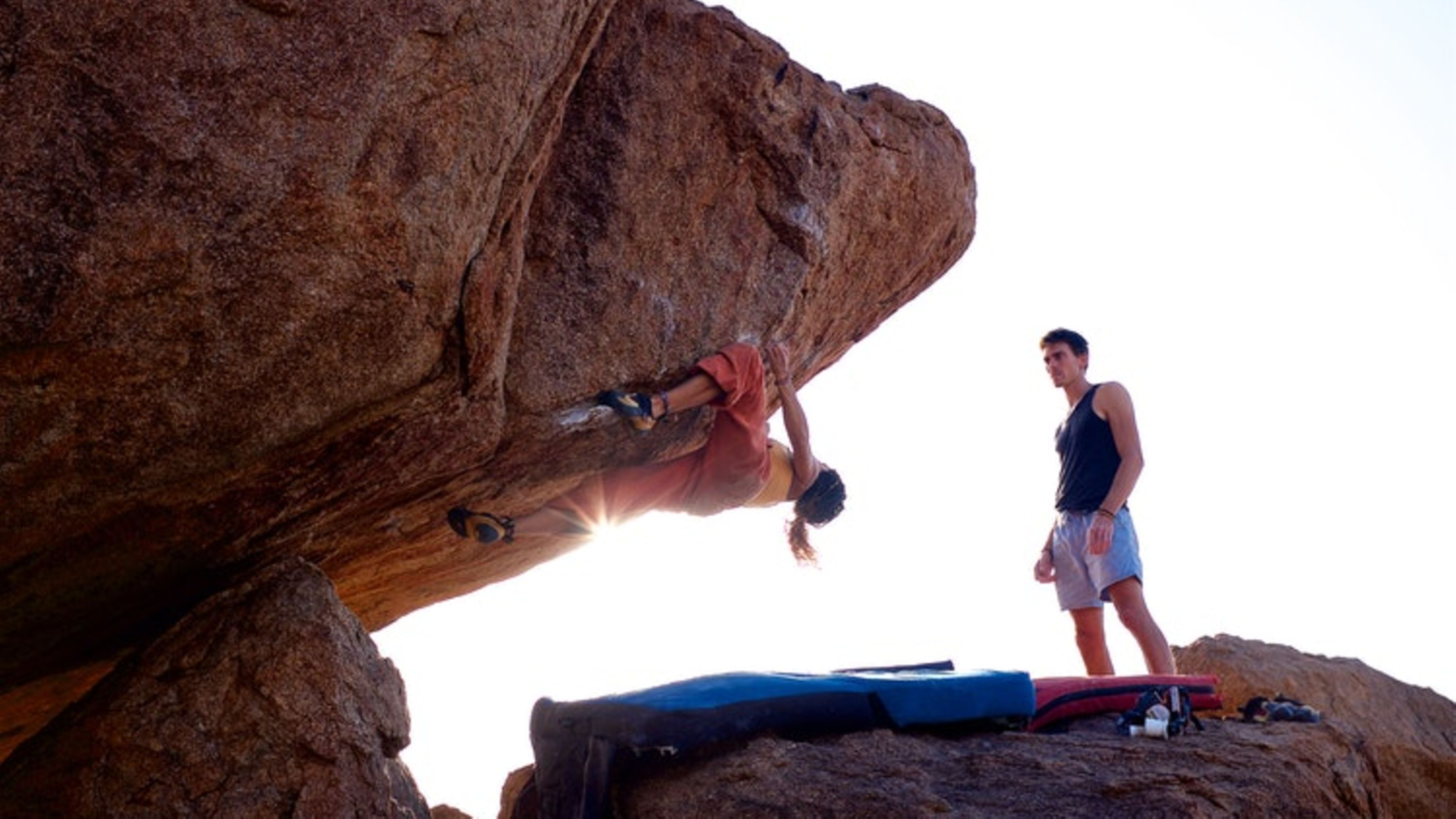 2 climbers, one secures, while the other climbs a rock