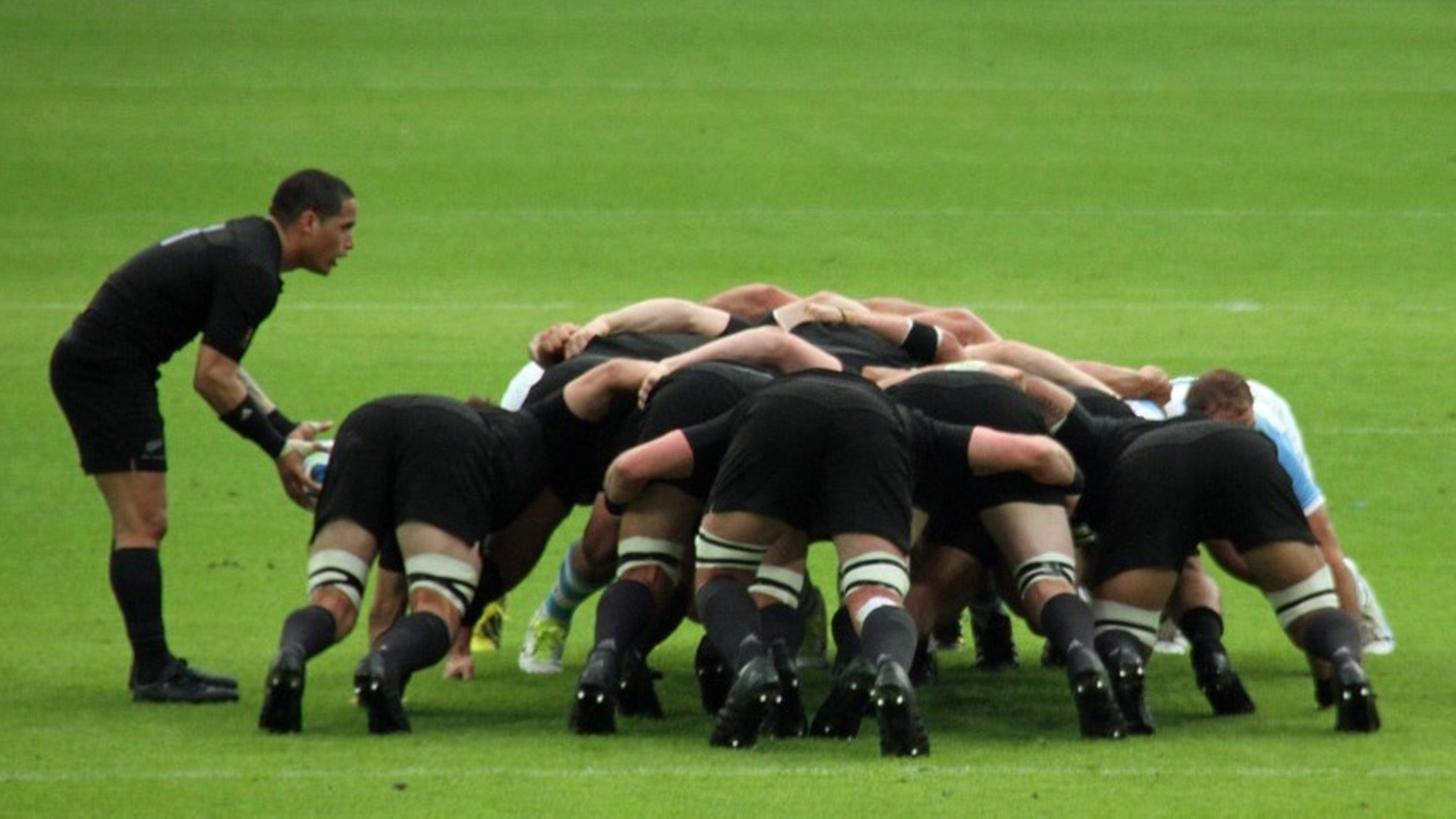 Rugby players standing in formation performing a scrum during a game