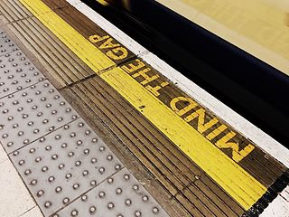 """mind the gap"" printed in subway station with incoming train"