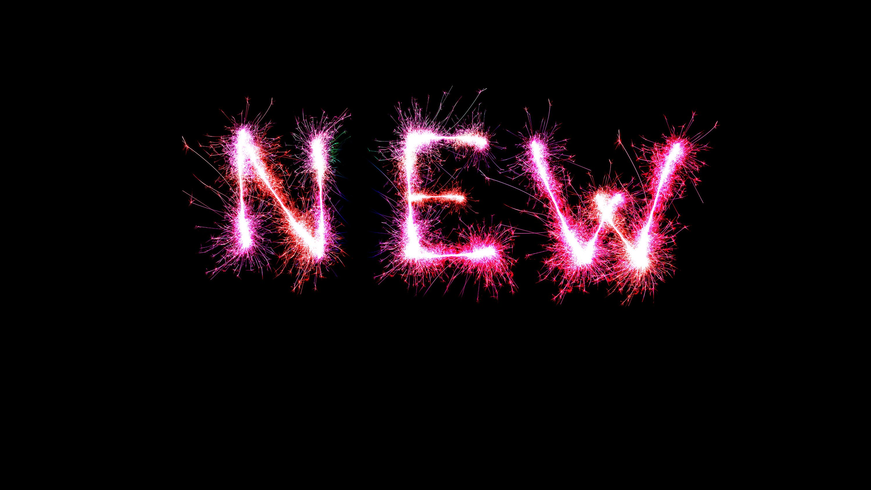 "Symbol image: The word ""new,"" formed from sparklers."