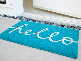 "An open front door and a doormat with the writing ""Hello""."