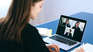 Woman is sitting in front of the laptop and is taking part in a video conference