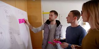 3 people with post-its in front of a whiteboard